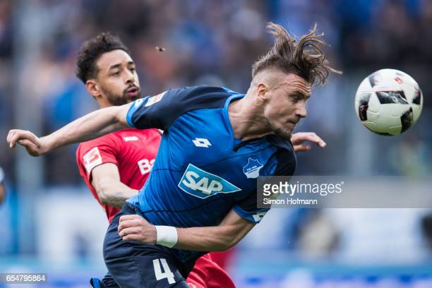 Ermin Bicakcic of Hoffenheim is challenged by Karim Bellarabi of Leverkusen during the Bundesliga match between TSG 1899 Hoffenheim and Bayer 04...