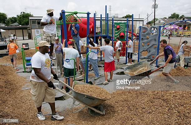 Ernest Allen of the Philadelphia Soul pushes a wheelbarrow of mulch during a playground building at the JW Johnson Elementary School prior to the...