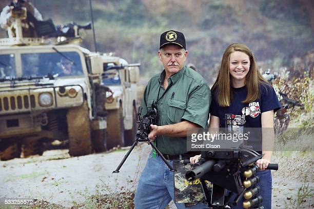 Ernest Belcher poses for a picture with an FN MK 48 machine gun while his daughter Morgan poses with a MK 19 grenade launcher at the NRA Annual...