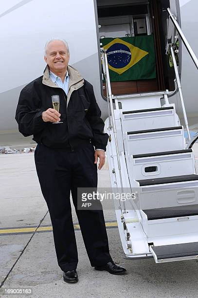 Ernest Edwards President of Embraer Executive Jets holds a glass of champagne as he poses with a Brazilian flag in front of the Business jet Embraer...