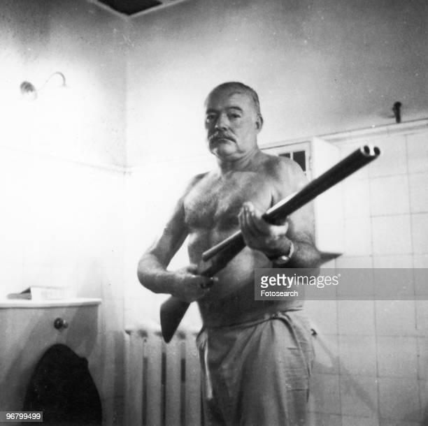 Ernest Hemingway standing with shotgun indoors circa 1950s