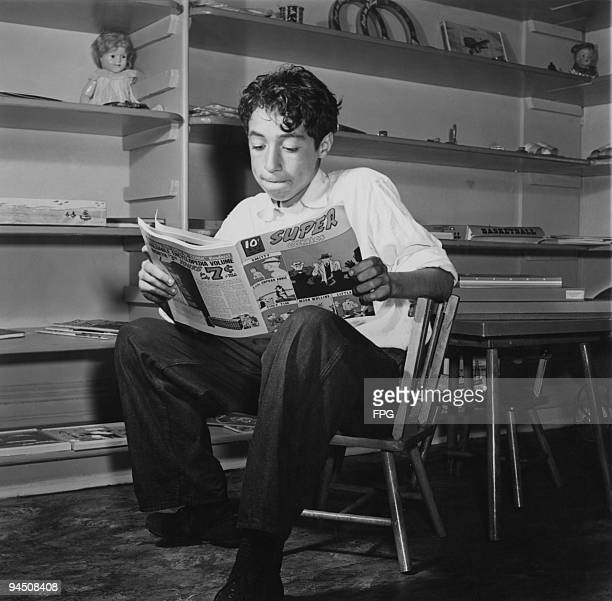 Ernest Woods reading a copy of 'Super Comics' at a toy library Harlem New York City circa 1960