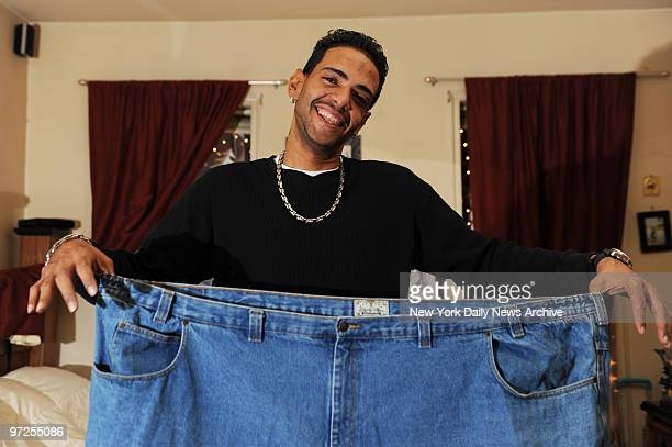 Ernesto Suncar holds a pair jeans he used to wear before losing over 400 pounds after a gastric bypass procedure