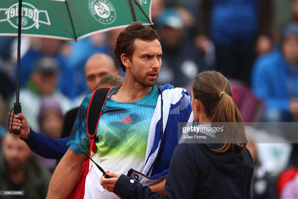<a gi-track='captionPersonalityLinkClicked' href=/galleries/search?phrase=Ernests+Gulbis&family=editorial&specificpeople=4095282 ng-click='$event.stopPropagation()'>Ernests Gulbis</a> of Latvia attempts to walk off court because of the falling rain, but is stopped by the Umpire during the Men's Singles fourth round match against David Goffin of Belgium on day ten of the 2016 French Open at Roland Garros on May 31, 2016 in Paris, France.