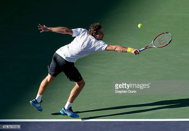 Ernests Gulbis of Latvia hits a return to John Isner during the BNP Paribas Open at Indian Wells Tennis Garden on March 14 2014 in Indian Wells...