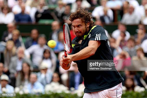Ernests Gulbis of Latvia returns a shot in his men's singles match against Roger Federer of Switzerland on day eight of the French Open at Roland...