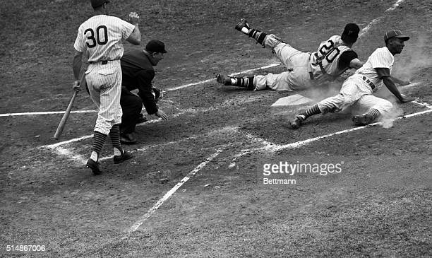 Ernie Banks of the Chicago Cubs scores from third base in the second inning of a ChicagoPittsburgh game at Wrigley Field Banks scored on Dale Long's...