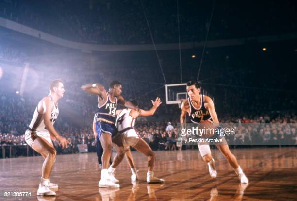 Ernie Beck of the Philadelphia Warriors dribbles the ball as his teammate Woody Sauldsberry sets a pick on Carl Braun of the New York Knicks as he...