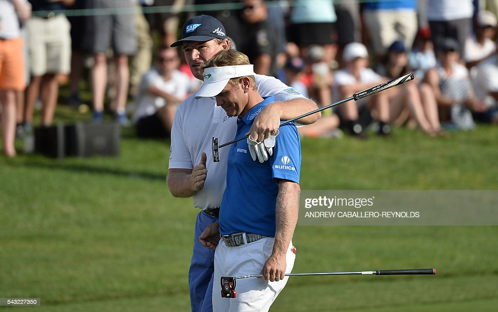 Ernie Els (L) hugs Billy Hurley III on the 18th green during the Quicken Loans National at Congressional Country Club in Bethesda, Maryland on June 26, 2016. / AFP / ANDREW