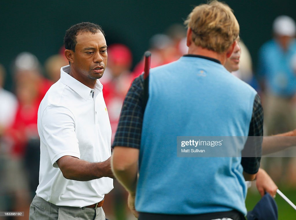 Ernie Els of South Africa and the International Team shakes hands with Tiger Woods of the U.S. Team after their weather-delayed Day Three Foursome Match at the Muirfield Village Golf Club on October 6, 2013 in Dublin, Ohio.