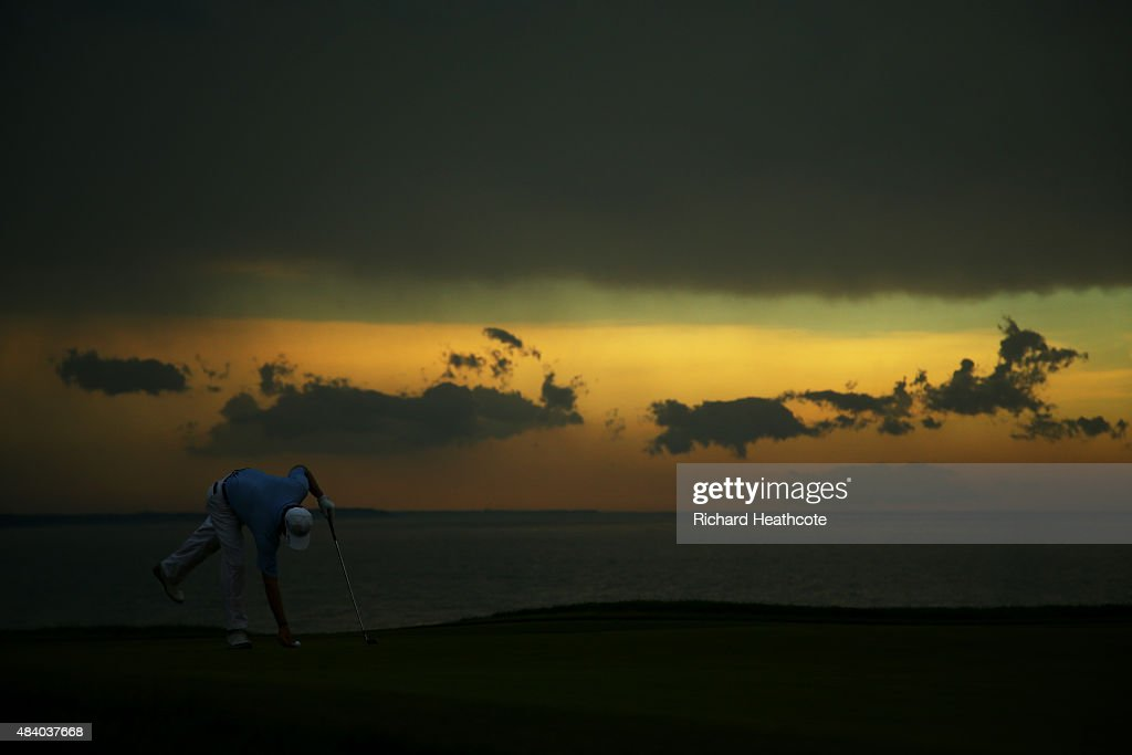 Ernie Els of South Africa marks his ball on the 16th green as lightning stops play during the second round of the 2015 PGA Championship at Whistling Straits on August 14, 2015 in Sheboygan, Wisconsin.