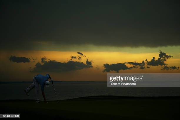 Ernie Els of South Africa marks his ball on the 16th green as lightning stops play during the second round of the 2015 PGA Championship at Whistling...