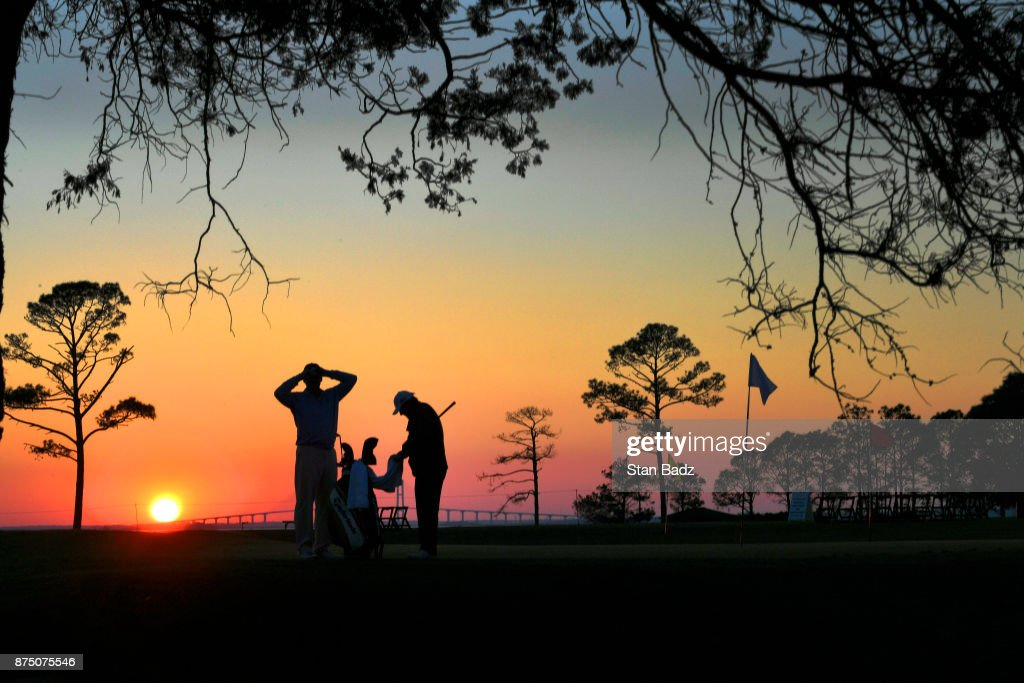 Ernie Els of South Africa with his caddie Cayce Kerr finish hitting chip shots on the practice area at sunset after the first round of The RSM Classic at the Sea Island Resort Seaside Course on November 16, 2017 in Sea Island, Georgia.