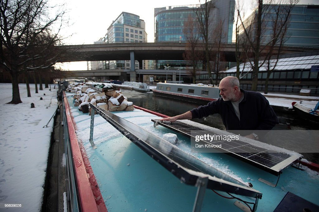 Ernie Williams clears the ice off solar panels on his canal boat on Regents Canal on January 8 2010 in London United Kingdom The UK recorded it's...