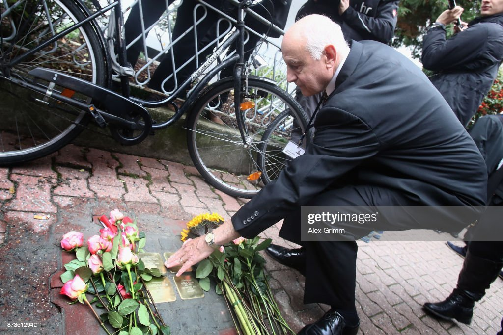 Ernst Ludwig Heineman a member of the scattered Cohn family lays down a flower after German artist Gunter Demnig layed four 'stumbling stones' to commemorate Jewish schoolgirl and Holocaust victim Karolina Cohn and her family outside the building where they once lived on November 13, 2017 in Frankfurt, Germany. Karolina's fate came to light after Israeli archeologists digging at the former World War II Sobibor concentration camp found an amulet inscribed with Karolina's birthdate and birthplace, which helped them to confirm that she and her family were killed there. The Nazis deported Karolina, then 12, and her family to Minsk in 1941, though the rest of their journey had been unknown until now. Approximately 30 members of the Cohn family came from the United States, Israel, Japan and Canada to attend today's ceremonies. 'Stumbling stones,' in German called 'Stolpersteine,' are commemorative cobblestones affixed with a brass plate with the names of victims laid in the sidewalks outside the former residences of Jews in Germany killed in the Holocaust.