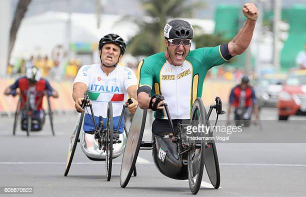 Ernst van Dyk of South Africa celebrates winning the gold medal while Alessandro Zanardi of Italy shows his dejeciton after competing in the Men's...