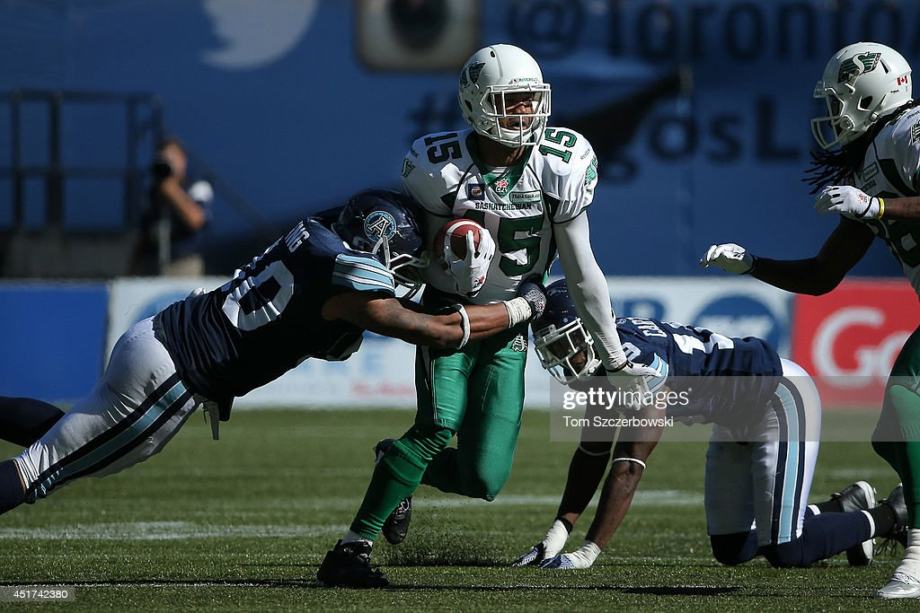 Eron Riley #15 of the Saskatchewan Roughriders runs with the ball as Cleyon Laing #90 of the Toronto Argonauts makes the tackle during a CFL game on July 5, 2014 at Rogers Centre in Toronto, Ontario, Canada.