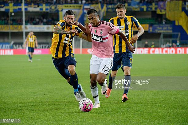 Eros Pisano of Hellas Verona competes with Alex Sandro of Juventus FC during the Serie A match between Hellas Verona FC and Juventus FC at Stadio...