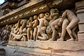 Erotic scene on sculptured surface of famous indian temple of Khajuraho. UNESCO Heritage site, built between 950 and 1150 in India, belong to two different religions - Hinduism and Jainism.