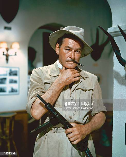 Errol Flynn Australian actor poses in costume holding a rifle and smoking a cigarette in a publicity still issued for the film 'The Roots of Heaven'...