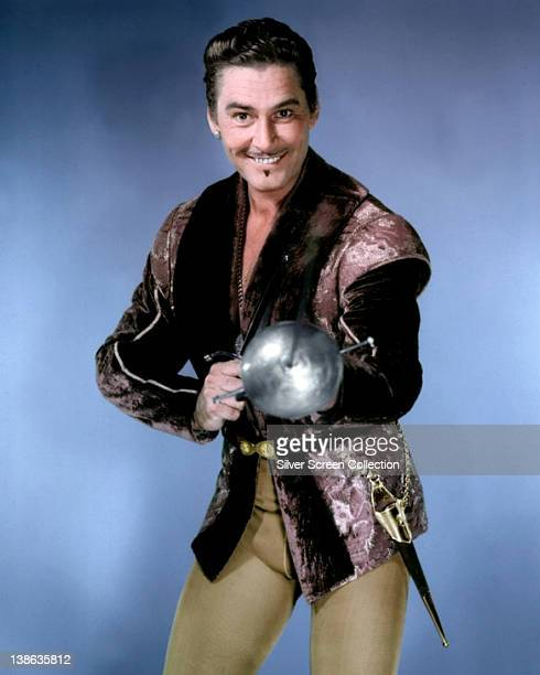 Errol Flynn Australian actor poses in costume pointing a sword towards the camera in a publicity portrait circa 1950