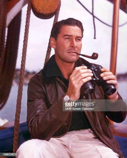 Errol Flynn Australian actor wearing a brown leather jacket and smoking a pipe while holding a pair of binoculars 1950