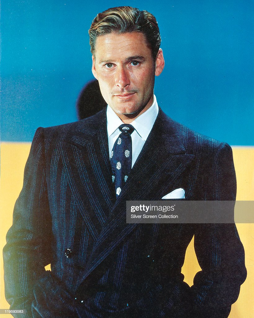 <a gi-track='captionPersonalityLinkClicked' href=/galleries/search?phrase=Errol+Flynn&family=editorial&specificpeople=93362 ng-click='$event.stopPropagation()'>Errol Flynn</a> (1909-1959), Australian actor, wearing a dark blue jacket, white shirt, and blue tie with white motifs in a studio portrait, with a blue background, circa 1945.