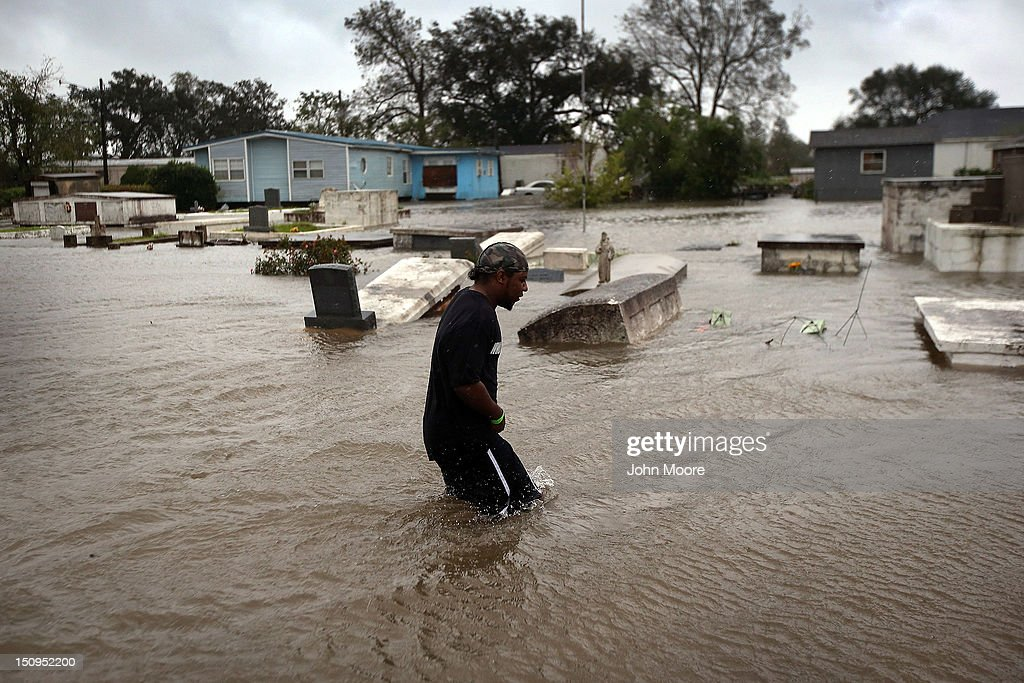 Errol Ragas walks past a cemetery to recover dry blankets from his home as rising waters from Hurricane Isaac flood his neighborhood on August 29, 2012 in Oakville, in Plaquemines Parish, Louisiana. The parish, south of New Orleans, was the most heavily damaged by the hurricane. The system, which was downgraded to a tropical storm by the National Weather Service, moved slowly across the state, dumping large amounts of rain and knocking out power to half a million Louisianans.