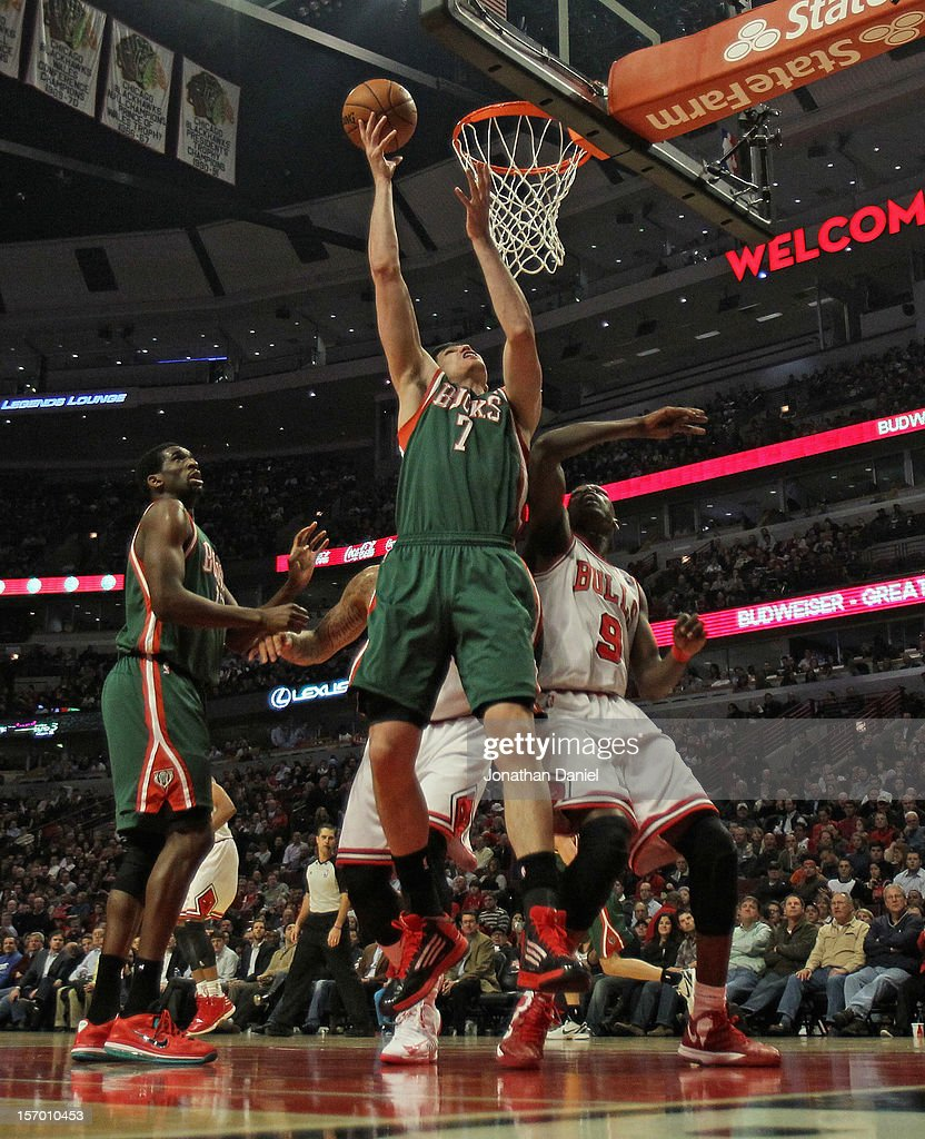 Ersan Ilyasova #7 of the Milwaukee Bucks rebounds over Loul Deng #9 and Carlos Boozer #5 of the Chicago Bulls at the United Center on November 26, 2012 in Chicago, Illinois. The Bucks defeated the Bulls 93-92.
