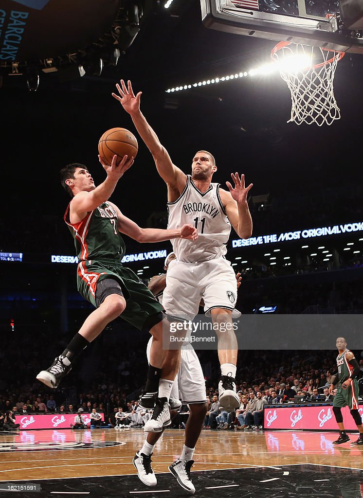 <a gi-track='captionPersonalityLinkClicked' href=/galleries/search?phrase=Ersan+Ilyasova&family=editorial&specificpeople=557070 ng-click='$event.stopPropagation()'>Ersan Ilyasova</a> #7 of the Milwaukee Bucks scores two in the first half as <a gi-track='captionPersonalityLinkClicked' href=/galleries/search?phrase=Brook+Lopez&family=editorial&specificpeople=3847328 ng-click='$event.stopPropagation()'>Brook Lopez</a> #11 of the Brooklyn Nets defends at the Barclays Center on February 19, 2013 in New York City.