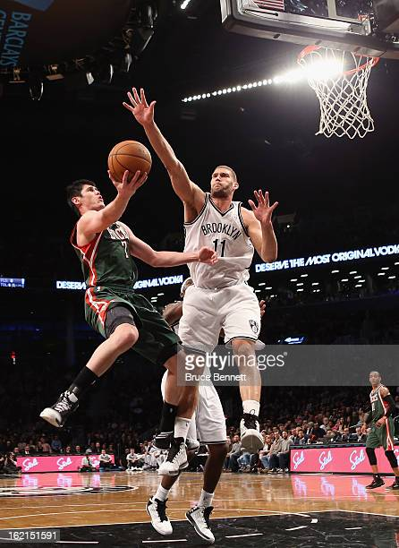 Ersan Ilyasova of the Milwaukee Bucks scores two in the first half as Brook Lopez of the Brooklyn Nets defends at the Barclays Center on February 19...