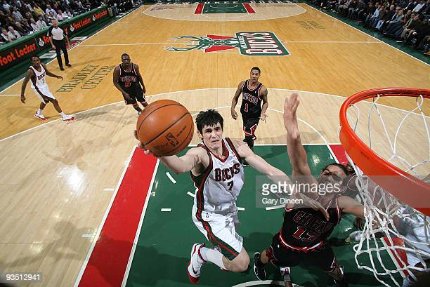 Ersan Ilyasova of the Milwaukee Bucks shoots a layup against Joakim Noah of the Chicago Bulls on November 30 2009 at the Bradley Center in Milwaukee...