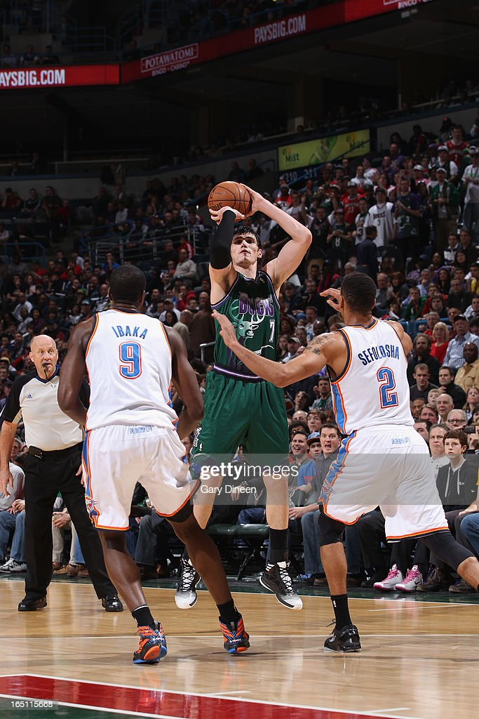 Ersan Ilyasova #7 of the Milwaukee Bucks shoots a three-pointer against <a gi-track='captionPersonalityLinkClicked' href=/galleries/search?phrase=Serge+Ibaka&family=editorial&specificpeople=5133378 ng-click='$event.stopPropagation()'>Serge Ibaka</a> #9 and Thabo Sefolosha #2 of the Oklahoma City Thunder on March 30, 2013 at the BMO Harris Bradley Center in Milwaukee, Wisconsin.