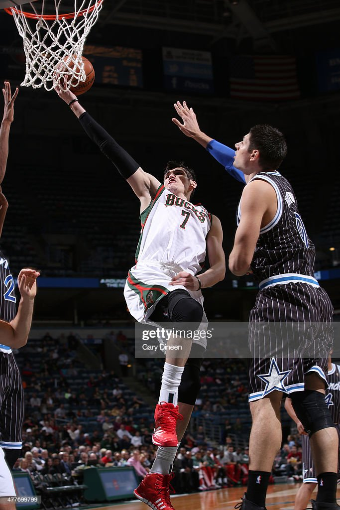 Ersan Ilyasova #7 of the Milwaukee Bucks shoots against (L-R) Maurice Harkless #21 and Nikola Vucevic #9 of the Orlando Magic on March 10, 2014 at the BMO Harris Bradley Center in Milwaukee, Wisconsin.