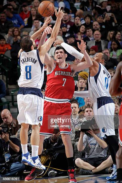 Ersan Ilyasova of the Milwaukee Bucks trys to pass the ball against Jose Calderon of the Dallas Mavericks on December 14 2013 at the American...
