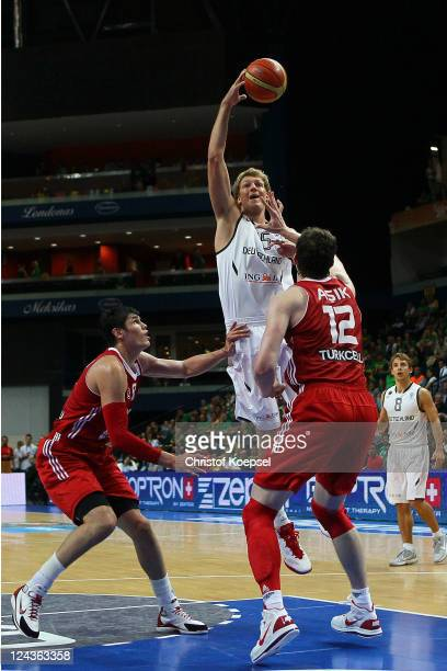 Ersan Ilyasova of Turkey and Oemer Asik of Turkey defend against JanHendrik Jagla of Germany during the EuroBasket 2011 second round group E match...