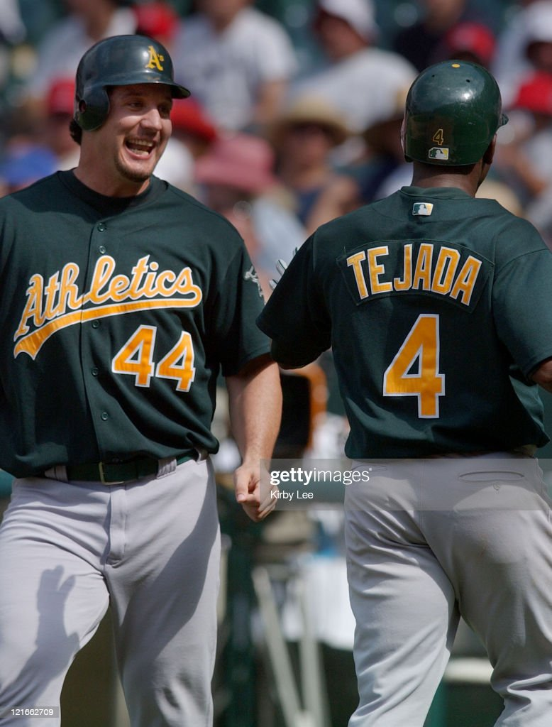 Erubiel Durazo of the Oakland Athletics greets Miguel Tejada after they scored in the ninth inning on a double by Eric Chavez The Athletics defeated...