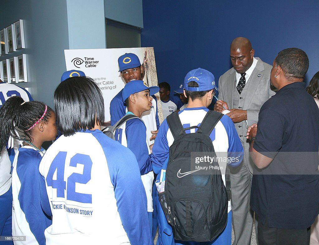Ervin 'Magic' Johnson (R) sign baseballs for Crenshaw High School Baseball team during Time Warner Cable & ASPIRE Partner to give a Southern California High School Student the opportunity to win a scholarship event at Dodger Stadium on April 15, 2013 in Los Angeles, California.