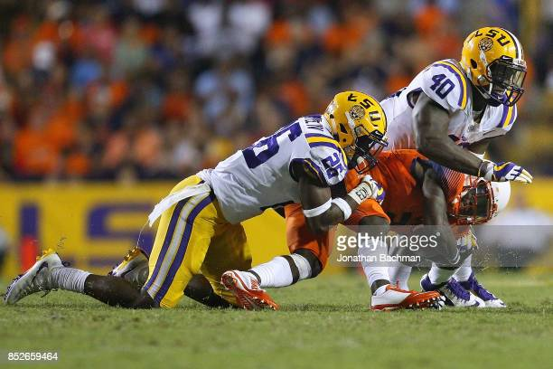 Ervin Philips of the Syracuse Orange is tackled by John Battle of the LSU Tigers and Devin White during the second half of a game at Tiger Stadium on...