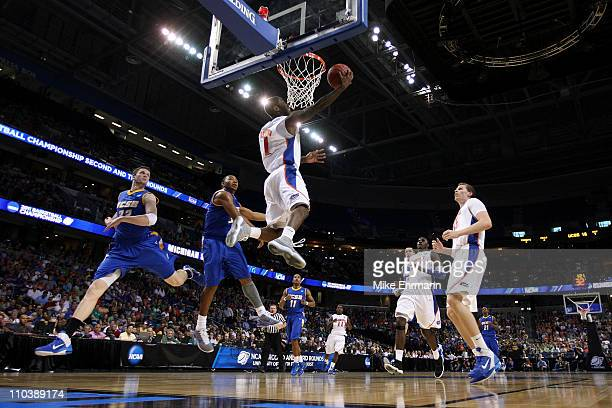 Erving Walker of the Florida Gators drives for a shot attempt against Orlando Johnson of the UC Santa Barbara Gauchos during the second round of the...