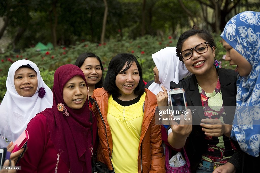 <a gi-track='captionPersonalityLinkClicked' href=/galleries/search?phrase=Erwiana+Sulistyaningsih&family=editorial&specificpeople=12341887 ng-click='$event.stopPropagation()'>Erwiana Sulistyaningsih</a> (C) is mobbed by well-wishers as she walks through Victoria Park in the Causeway Bay district of Hong Kong on March 1, 2015. As she walks through Hong Kong's Victoria Park on a busy Sunday afternoon, <a gi-track='captionPersonalityLinkClicked' href=/galleries/search?phrase=Erwiana+Sulistyaningsih&family=editorial&specificpeople=12341887 ng-click='$event.stopPropagation()'>Erwiana Sulistyaningsih</a> is stopped every few steps for photos and hugs. Most of her fans are Indonesian domestic workers enjoying their weekly day off, gathering as they always do for food, dancing and a chat, but there are Hong Kong families too.