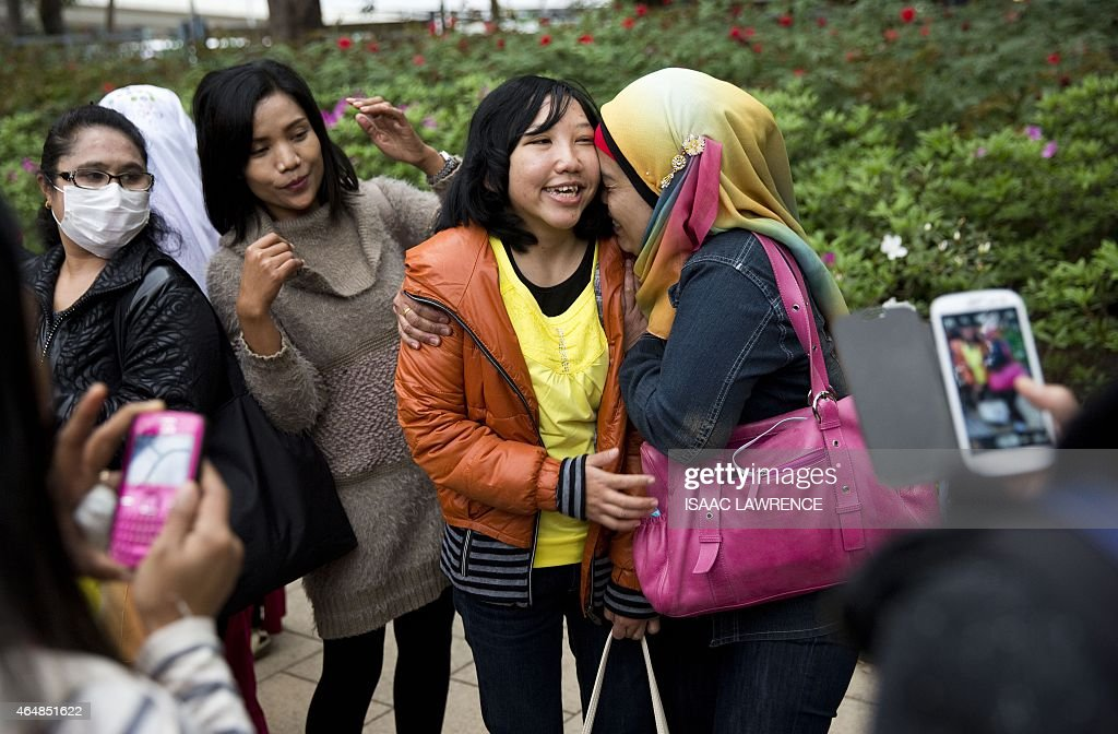 <a gi-track='captionPersonalityLinkClicked' href=/galleries/search?phrase=Erwiana+Sulistyaningsih&family=editorial&specificpeople=12341887 ng-click='$event.stopPropagation()'>Erwiana Sulistyaningsih</a> (C orange jacket) is mobbed by well-wishers as she walks through Victoria Park in the Causeway Bay district of Hong Kong on March 1, 2015. As she walks through Hong Kong's Victoria Park on a busy Sunday afternoon, <a gi-track='captionPersonalityLinkClicked' href=/galleries/search?phrase=Erwiana+Sulistyaningsih&family=editorial&specificpeople=12341887 ng-click='$event.stopPropagation()'>Erwiana Sulistyaningsih</a> is stopped every few steps for photos and hugs. Most of her fans are Indonesian domestic workers enjoying their weekly day off, gathering as they always do for food, dancing and a chat, but there are Hong Kong families too.