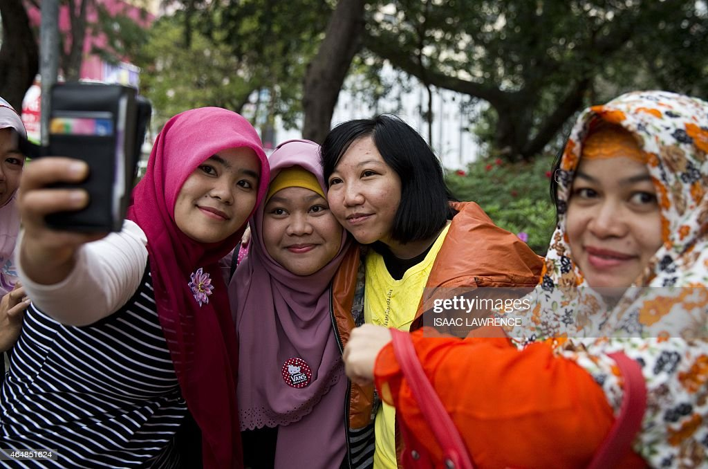 <a gi-track='captionPersonalityLinkClicked' href=/galleries/search?phrase=Erwiana+Sulistyaningsih&family=editorial&specificpeople=12341887 ng-click='$event.stopPropagation()'>Erwiana Sulistyaningsih</a> (C orange jacket) poses for photographs with well-wishers as she walks through Victoria Park in the Causeway Bay district of Hong Kong on March 1, 2015. As she walks through Hong Kong's Victoria Park on a busy Sunday afternoon, <a gi-track='captionPersonalityLinkClicked' href=/galleries/search?phrase=Erwiana+Sulistyaningsih&family=editorial&specificpeople=12341887 ng-click='$event.stopPropagation()'>Erwiana Sulistyaningsih</a> is stopped every few steps for photos and hugs. Most of her fans are Indonesian domestic workers enjoying their weekly day off, gathering as they always do for food, dancing and a chat, but there are Hong Kong families too.
