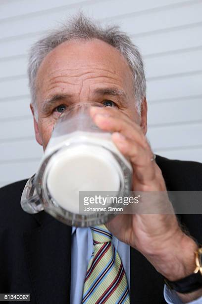 Erwin Huber head of the CSU and Bavarian Economic Minister drinks milk in front of the cow barn of milk farmer Hans Doeringer during a discussion...