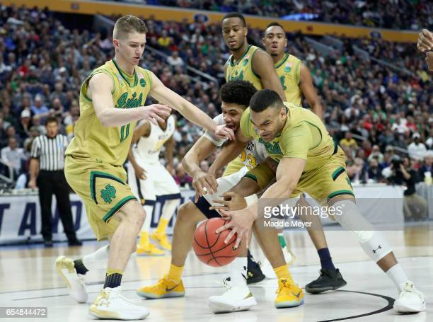 Esa Ahmad of the West Virginia Mountaineers battles for a loose ball against teammates Rex Pflueger and Austin Torres of the Notre Dame Fighting...