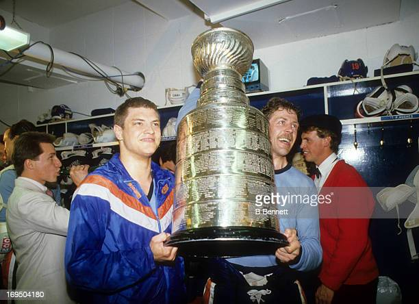 Esa Tikkanen and Willy Lindstrom of the Edmonton Oilers celebrate with the Stanley Cup Trophy in the locker room after the Oilers defeated the...
