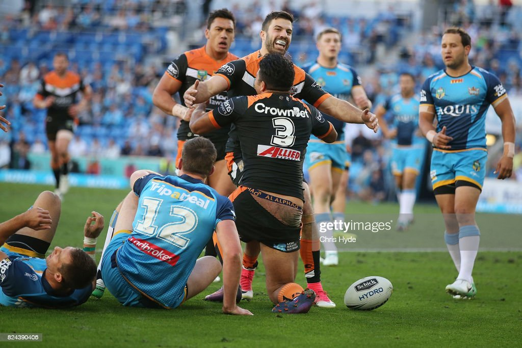 Esan Marsters of the Tigers celebrates a try with James Tedesco during the round 21 NRL match between the Gold Coast Titans and the Wests Tigers at Cbus Super Stadium on July 30, 2017 in Gold Coast, Australia.