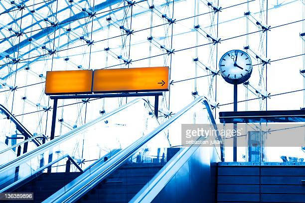 escalator sign and clock in front of modern office building