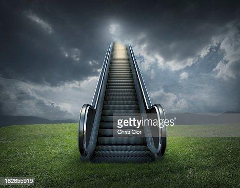 Escalator to cloudy sky in rural landscape