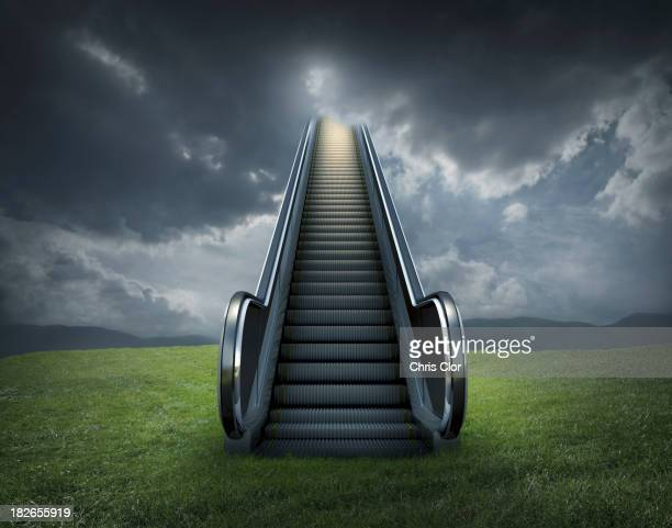 Escalator to cloudy sky in rural landscape